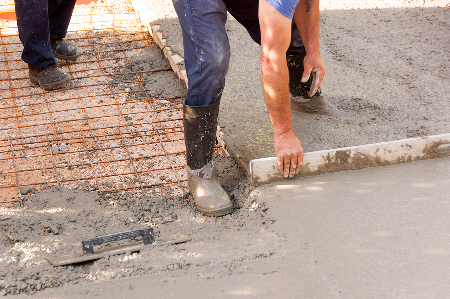 workers work on concreting parking spaces in front of the house. mason worker leveling concrete with trowels mason hands spreading poured concrete.