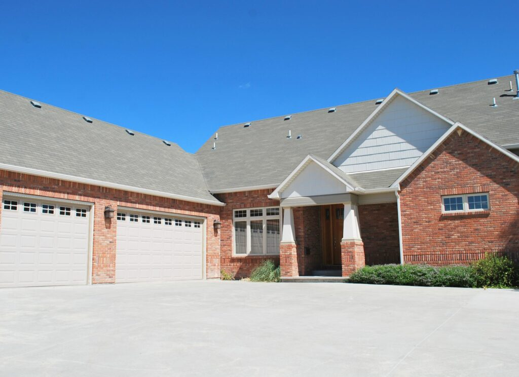 brick type house with concrete driveway