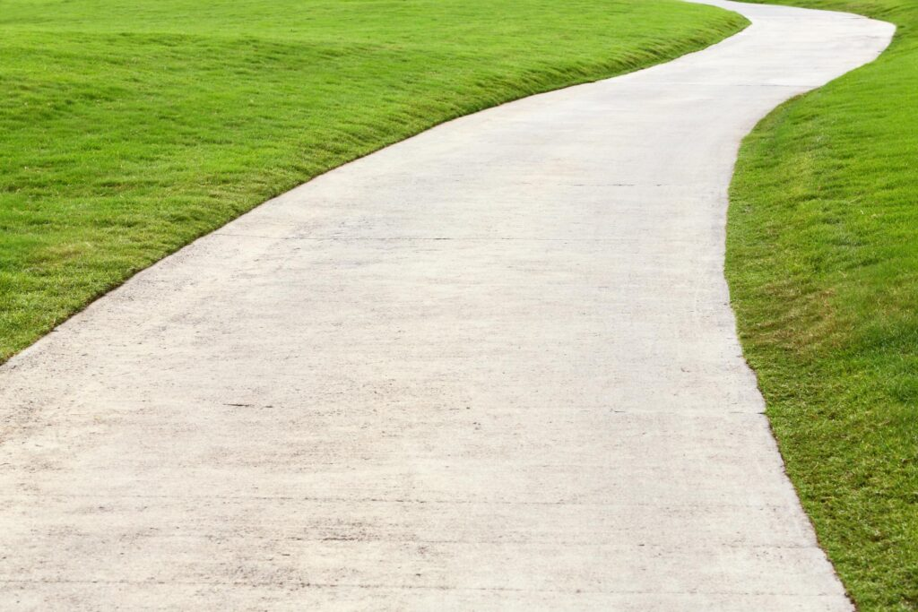 a concrete sidewalk with grass on the sides